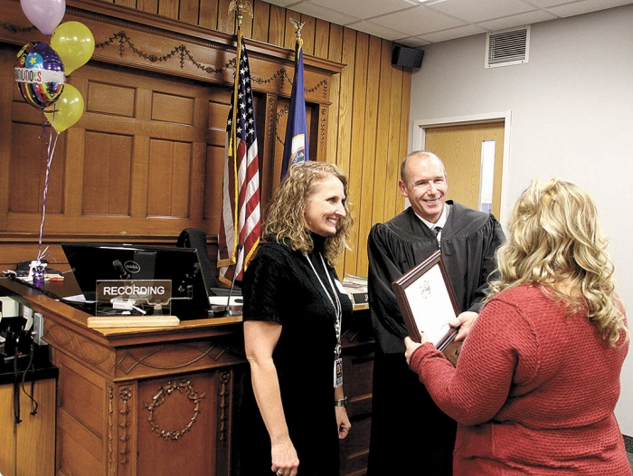 a man in judges robes and a woman in black smile, shake hands, and hand a certificate to a woman in red