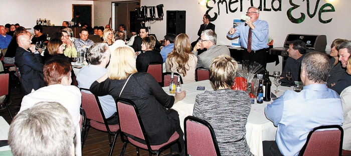 Some of the 222 people who attended Emerald Eve Friday night bid on items being auctioned by Bob Zielsdorf.