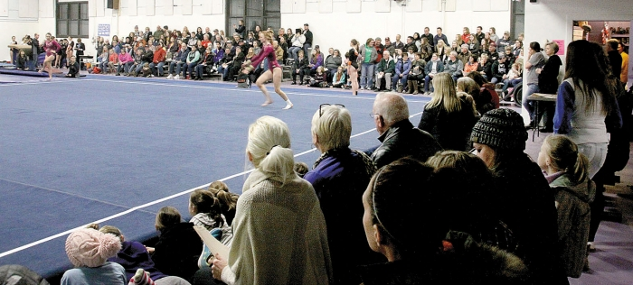 Benson gymnasts, coaches, members of the visiting team, and spectators crowd along the cramped space of the Benson Armory for a gymnastics meet.