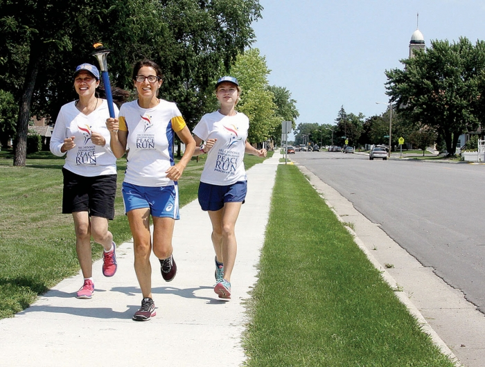 Putu from Indonesia, Nayaja from Italy, and Kshema from Ukraine run with the Sri Chinmoy Oneness-Home Peace Run torch as they pass through Benson last Friday.