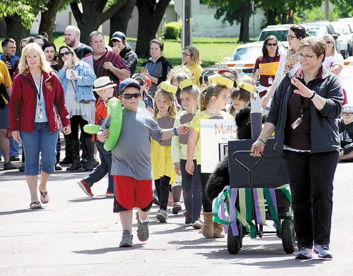 "After 37 years of teaching in the Benson elementary schools teacher Donna Tatge is retiring. She waves goodbye as she is followed by her first grade class, which read ""Mother Bruce"" by Ryan T. Higgins. Paraprofessional Nettie Berens walks along with the class."