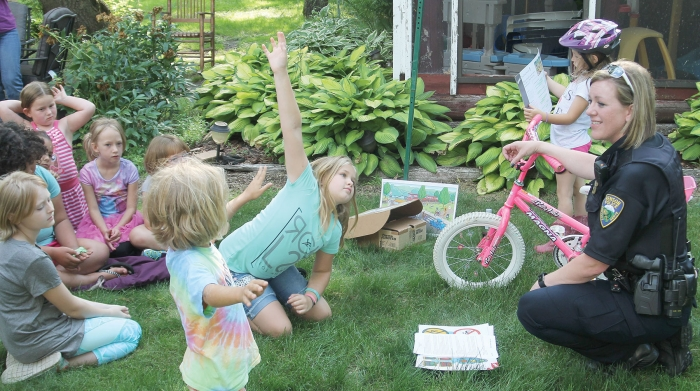 Benson Police Officer Paula Wilson (right) speaks with the local Girl Scouts about the importance of bike safety.  The Girl Scouts worked on their Cadette Safety, Junior Safety, or Daisy Safety pins (depending upon their age level) with the help of area adults and troop leaders.