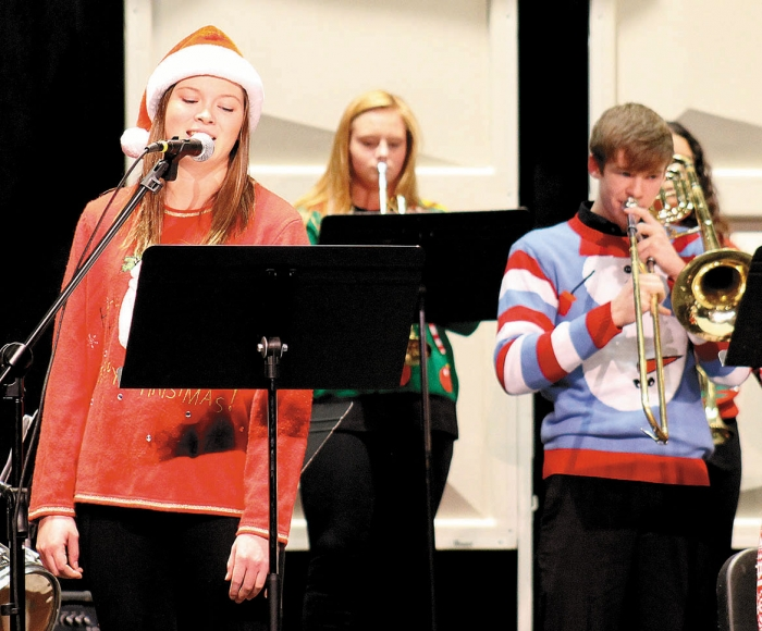 "Elizabeth Langan (left) sings ""Santa Baby"", while members of the Jazz I group perform in the background during the BHS ""A Jazzin' Holiday Concert,"" Monday night in the Junior High Auditorium.  In the background are trumpet player Gracie Grussing, and trombonist Nathan Habben (right)."
