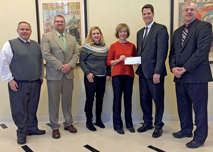 Minnesota's Lt. Governor Tina Smith (in red), presented Swift County and Federated Telephone Cooperative with a broadband grant check for $4.95 million Friday. Above are, from left, Mike Pogge-Weaver, Swift County Administrator; Erick Rudningen, Swift County Commissioner, District 5-Kerkhoven; Jennifer Frost, Swift County Rural Development Authority director; Lt. Gov. Smith; Kevin Beyer, General Manager of Federated Telephone; and Gary Hendrickx, Swift County Commissioner, District 1-Appleton.