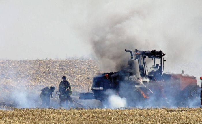Benson firemen put out the flames that engulf a Case quad-trac tractor. It is suspected that cornstalks became lodged in one of the tracks and caught fire.