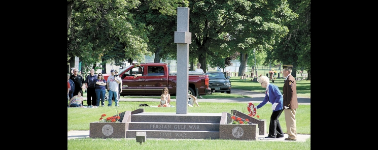 Helen Hollingsworth, escorted by Ben Hess, lays a wreath on the Benson City Cemetery War Veterans Memorial on Memorial Day in 2016.