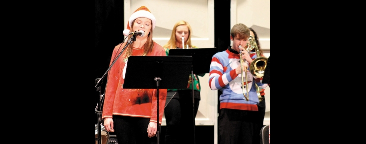 """Elizabeth Langan (left) sings """"Santa Baby"""", while members of the Jazz I group perform in the background during the BHS """"A Jazzin' Holiday Concert,"""" Monday night in the Junior High Auditorium.  In the background are trumpet player Gracie Grussing, and trombonist Nathan Habben (right)."""