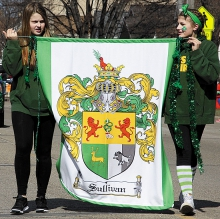Abby Saterbak and LuLu Bach carry the Sullivan family coat of arms banner in Saturday's parade.