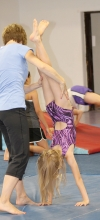 Benson-KMS head gymnastics coach Kathy Ahrndt helps a young gymnast do a handstand.