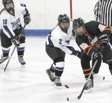 Kayla Benson (2) battles with an opponent for possession of the puck after a faceoff as teammate Nicole Berens (16) looks on from behind.